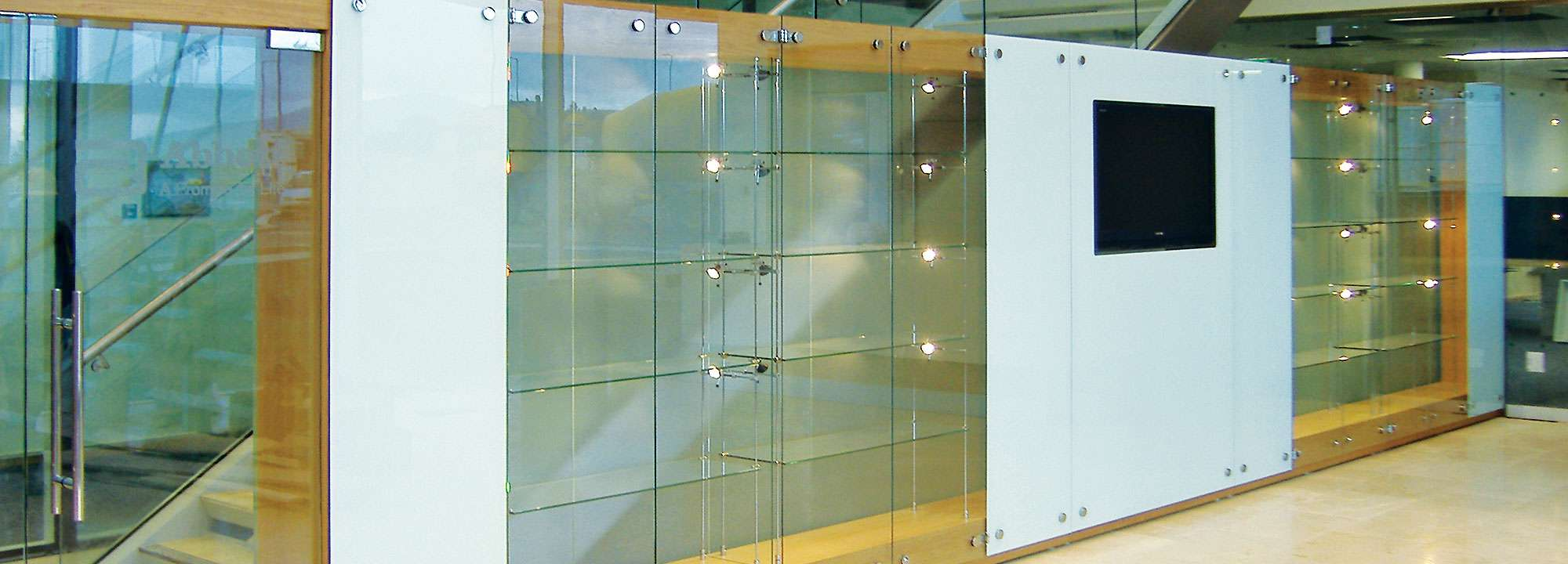 cabinet walls comprised of a combination of glass display cabinets and panels with low voltage lightning & Glass Cabinet Display Walls | Shopkit UK